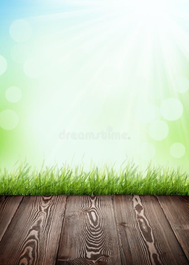De zomerachtergrond met houten vloer, groen gras en bokeh royalty-vrije stock afbeelding
