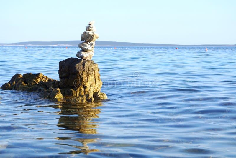 De zomerachtergrond met de overzeese oppervlakte van het kustlandschap en met rotsen en gestapelde stenen stock foto's