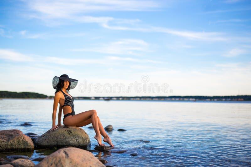 De zomerachtergrond - mooi model in bikini het stellen op beac stock afbeeldingen
