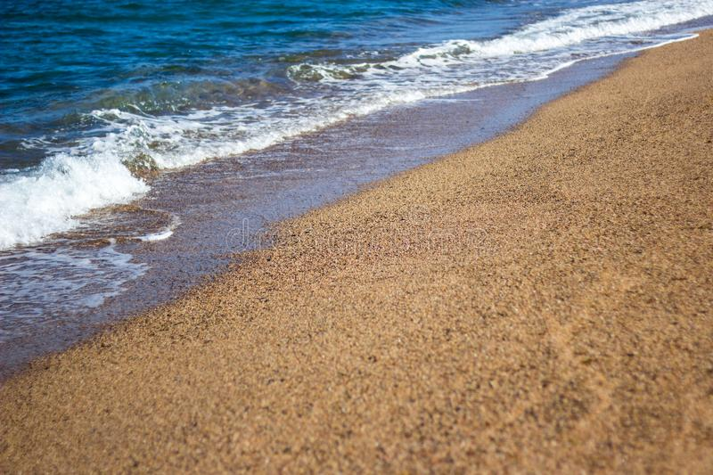 De zomerachtergrond - strand met gouden zand en overzeese golven stock afbeeldingen