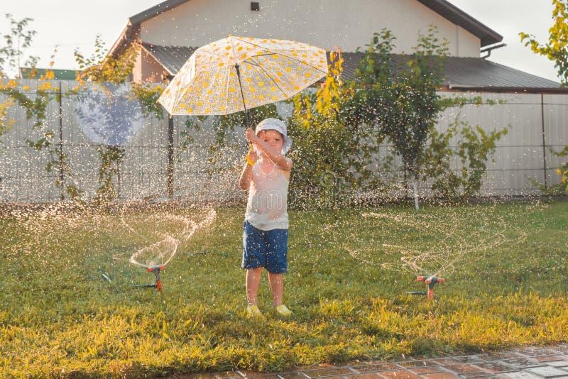 De zomeractiviteiten Openlucht spelen van kinderen Het gelukkige jongen spelen openlucht met het water geven van systeem De vakan royalty-vrije stock fotografie