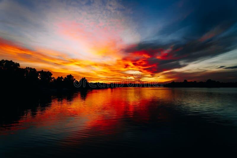 De zomeravond bij de rivier Stille en kalme avond De zon daalt langzaam onder de horizon Zonsondergang en schemering royalty-vrije stock foto