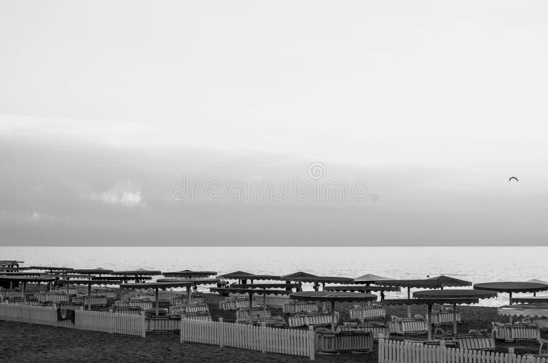De zomeravond op strand met gestreepte witte houten omheining stock afbeeldingen
