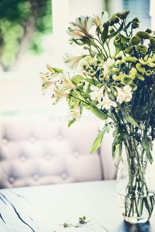 De de zomerbloemen bundelen in glasvaas op lijst in woonkamer met dalende bloemblaadjes Comfortabel huis royalty-vrije stock fotografie