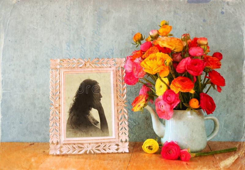 De zomerboeket van bloemen en victorian kader met uitstekend portret van jonge vrouw op de houten lijst beeld met geweven overl stock afbeelding