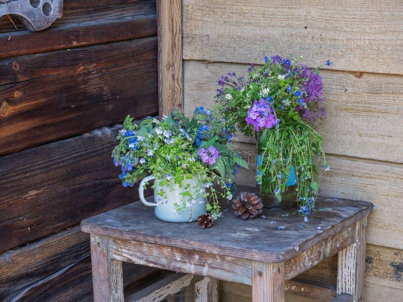 De zomerboeket van kleine wildflowers op een oude houten kruk op de portiek van een blokhuis royalty-vrije stock afbeelding