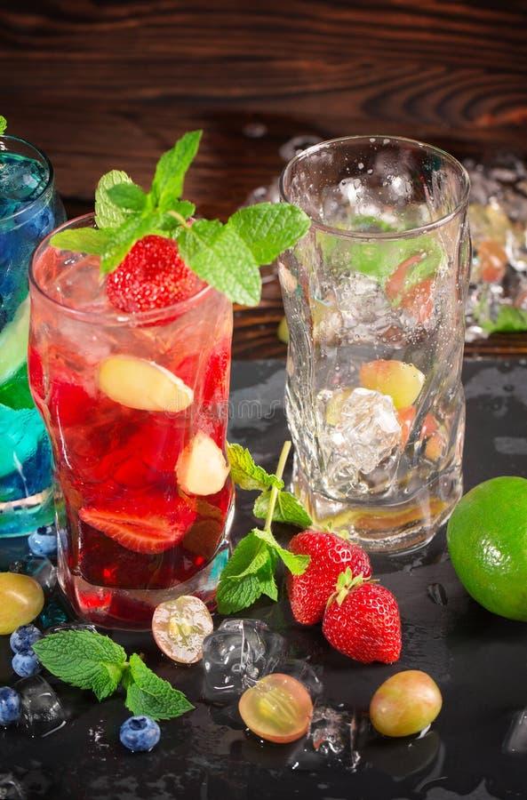 De zomercocktails met munt, bosbessen, aardbeien, druiven, ijs en alcoholische drank in glazen en een leeg glas op een houten ach stock afbeeldingen