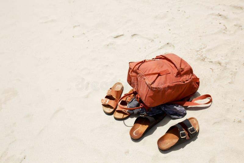De zomerconcept, dingen op strandzand, mannelijke en vrouwelijke ploffen en bruine sportenrugzak Vlak leg De ruimte van het exemp stock fotografie