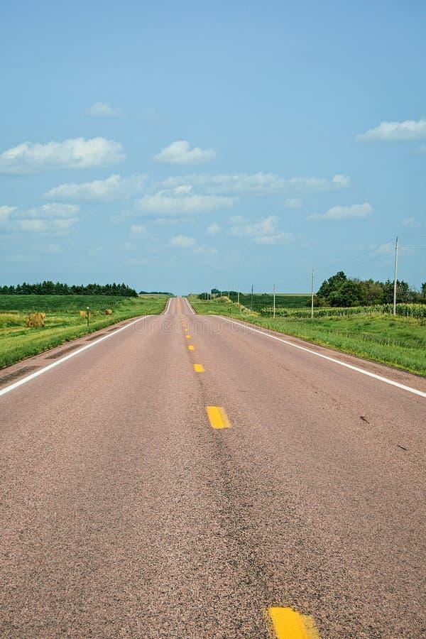 De zomerdag en een asfaltweg stock afbeeldingen