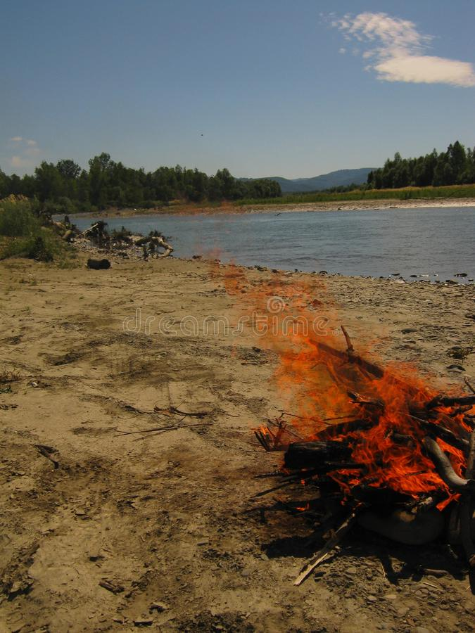 De zomerdag, vuur op de zandige bank van de rivier royalty-vrije stock afbeeldingen