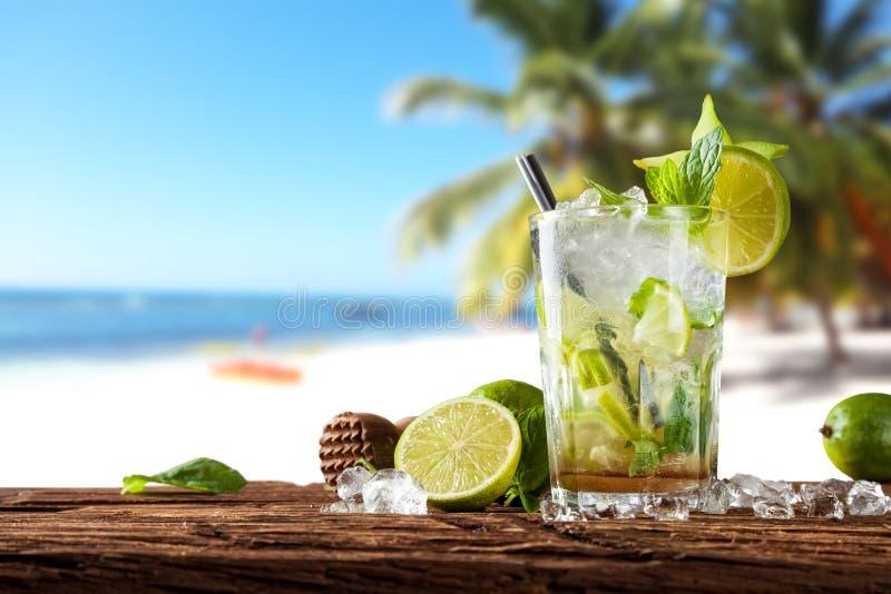 De zomerdrank met onduidelijk beeldstrand op achtergrond stock foto