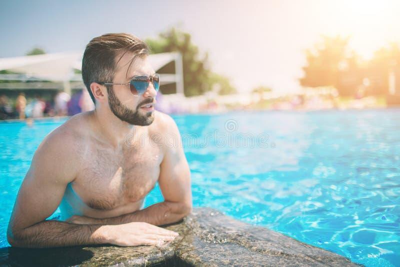 De zomerfoto van de spier glimlachende mens in zwembad Gelukkig mannelijk model in water op de zomervakanties royalty-vrije stock fotografie