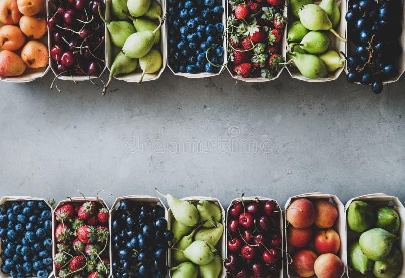 De zomerfruit en bessenassortiment in houten vakjes, exemplaarruimte stock afbeeldingen