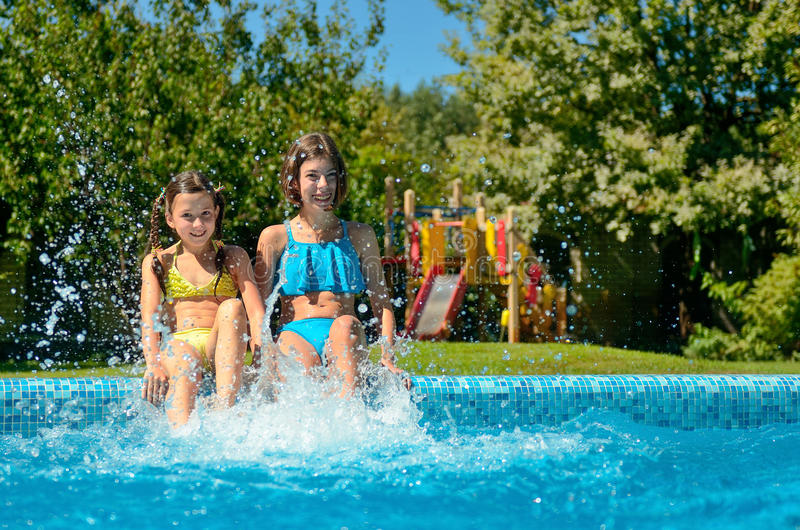 De de zomergeschiktheid, jonge geitjes in zwembad heeft pret, glimlachend meisjesplons in water royalty-vrije stock foto