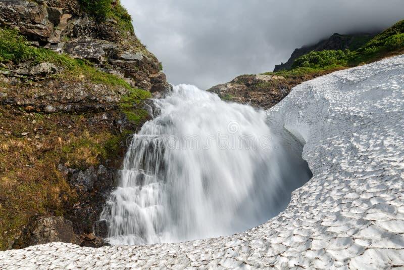 De zomerlandschap - bergwaterval die in snowfield vallen stock afbeelding