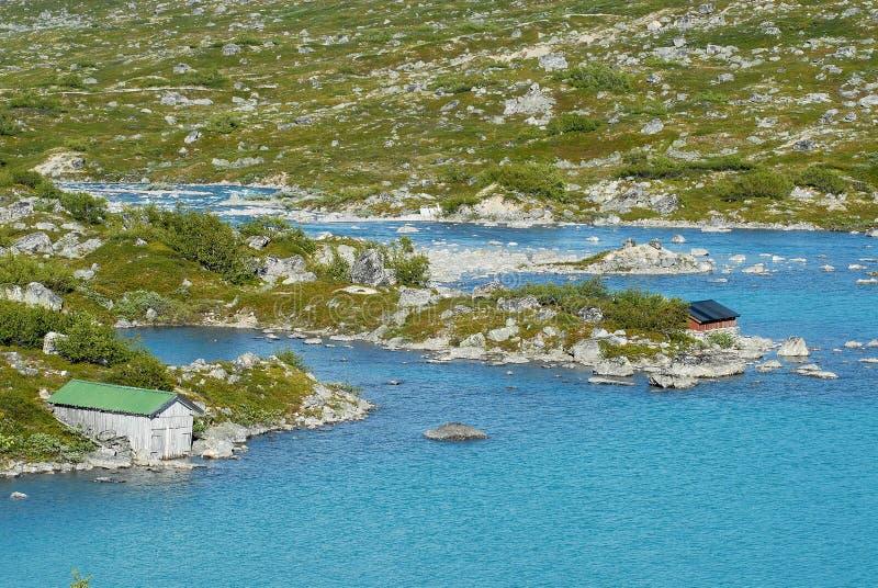 De zomerlandschap met traditionele plattelandshuisjes bij een meerkust in landelijk Noorwegen stock afbeeldingen