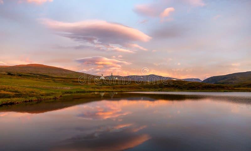 De zomerlandschap in toendra met een meer in bergen in zonsopgang royalty-vrije stock afbeelding