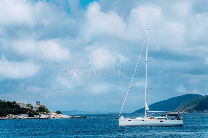 De zomerlandschap van haven Fiskardo Witte zeilboot in mooie rustige baai tegenover rotsachtige kust Schilderachtige openluchtscè stock afbeeldingen