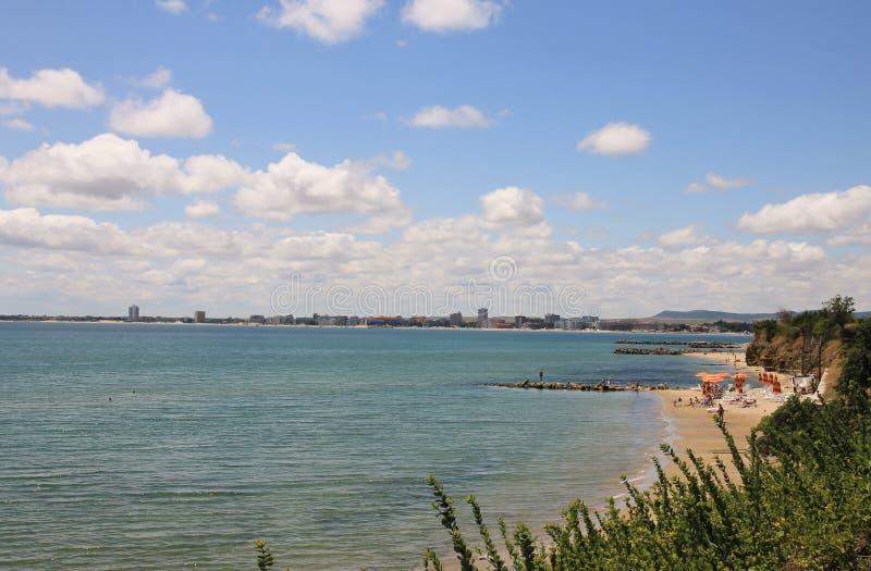 De zomerlandschap van het overzees en het groene gras Zandig strand en blauw water met hemel en witte wolken Zonnig strand in Bul stock afbeelding
