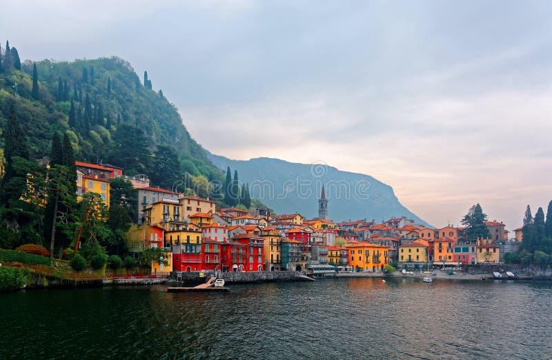 De zomerlandschap van Varenna, een mooi oever van het meerdorp door Meer Como, met een kerktoren stock foto's