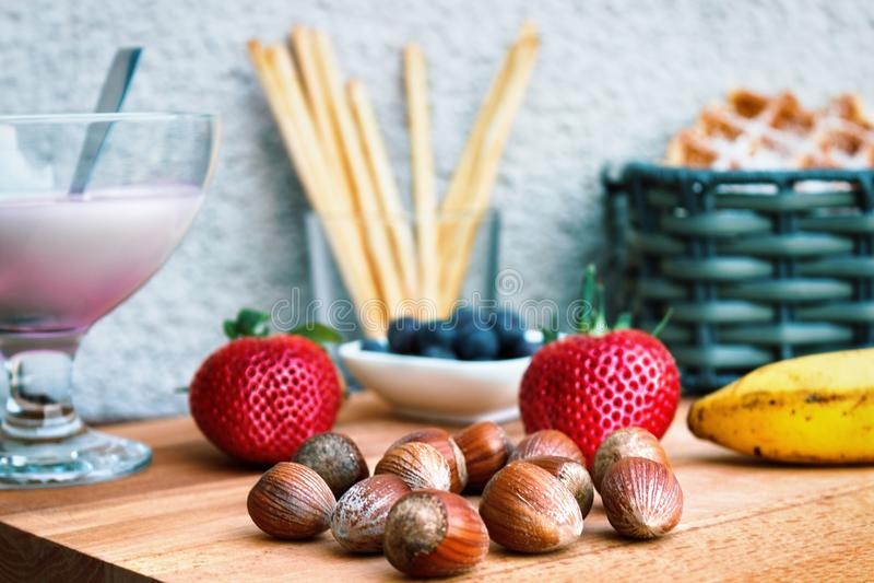 De zomermaaltijd met yoghurt, aardbeien, hazelnoten en pastery royalty-vrije stock foto