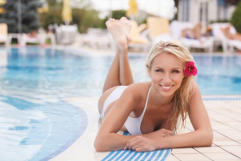 De zomermeisje. Aantrekkelijke jonge vrouwen in bikini die op de pools liggen stock foto's