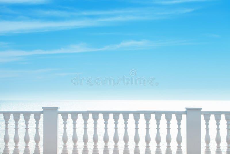 De zomermening die met klassieke witte balustrade en leeg terras het overzees overzien De zomerachtergrond toerisme royalty-vrije stock afbeelding