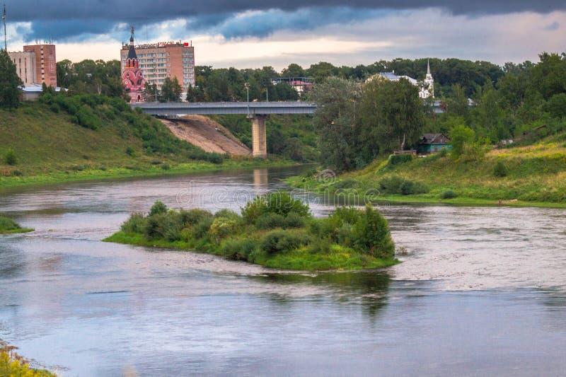 De zomermening van de majestueuze kalme waterstroom en de schilderachtige eiland en steile kust van de Volga rivier met brug in b royalty-vrije stock afbeelding