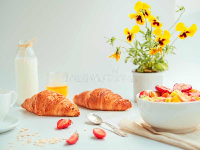De zomerontbijt met een kom gezonde verse fruitsalade, croissants, en melk Witte lijst met gele bloemen royalty-vrije stock afbeelding