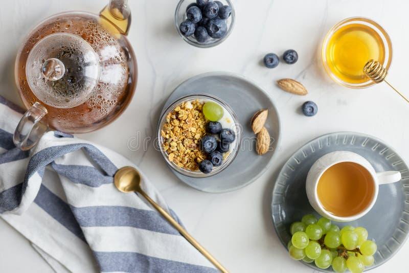 De zomerontbijt met granola, bosbes en druif met melk stock afbeeldingen