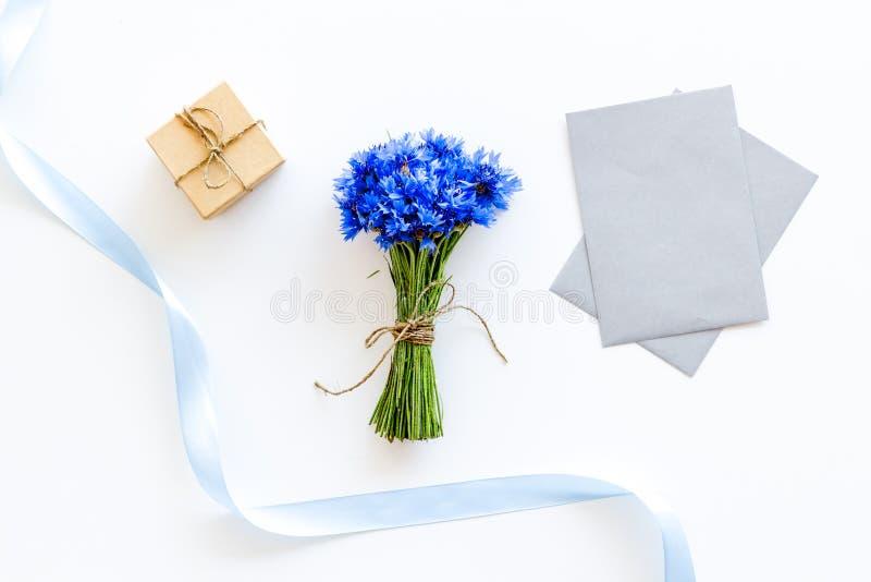 De zomerontwerp voor blog met boeket van blauwe korenbloemen, envelop en gift op witte hoogste mening als achtergrond copyspace stock fotografie