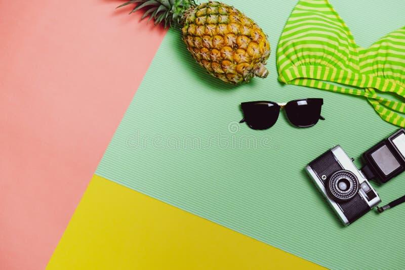 De zomerpartij De tijd te ontspannen gaat naar strand en reist met zonnebril, Camera, Bikini en Ananasfruit op Pastelkleurachterg royalty-vrije stock fotografie