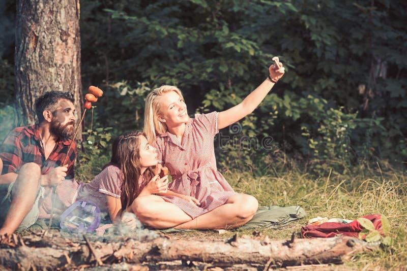De zomerpicknick in hout Glimlachend blond meisje die selfie in bos of park nemen Vrolijke vrienden die met worsten stellen voor royalty-vrije stock fotografie