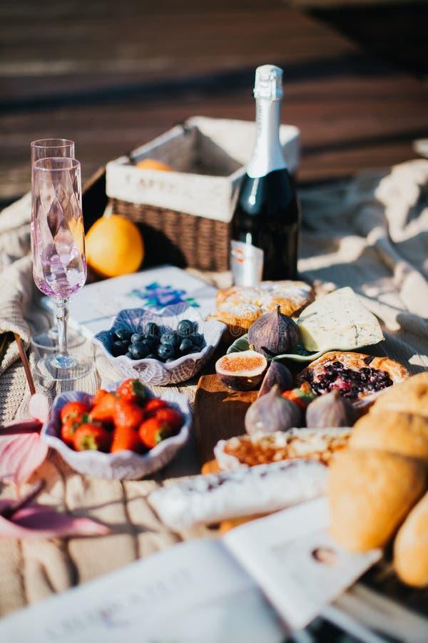 De zomerpicknick met een fles van uitstekende champagne en aardbeien stock fotografie