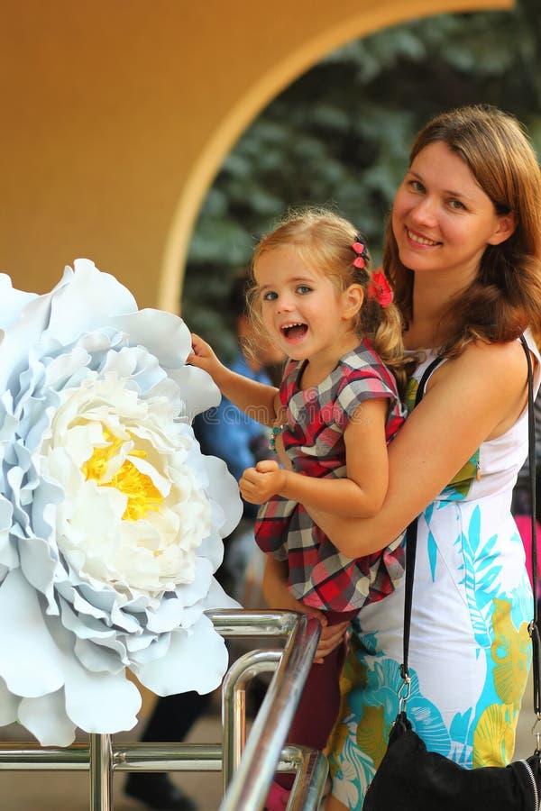 De zomerportret van een gelukkige glimlachende moeder en een dochter in feestelijke kleren met bloemen stock afbeelding