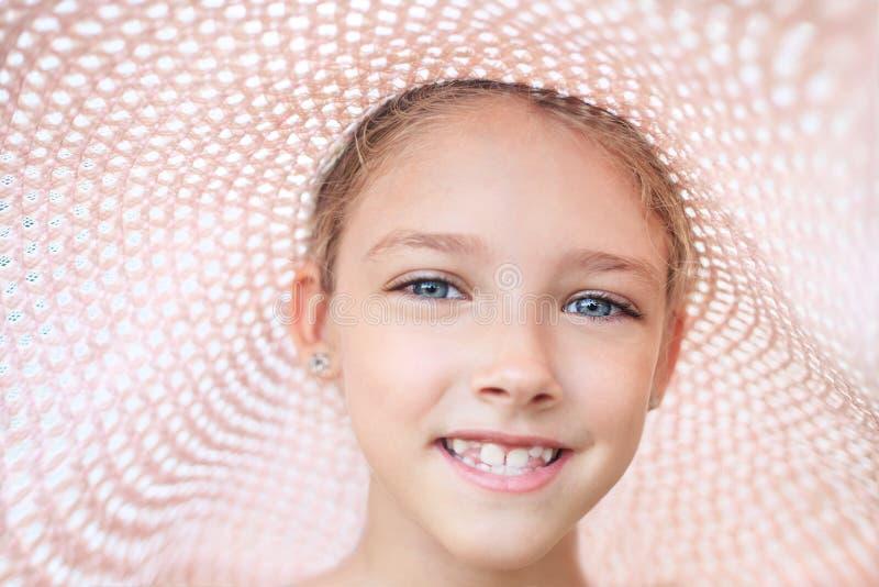 De zomerportret van een mooi meisje in een roze hoed stock foto's