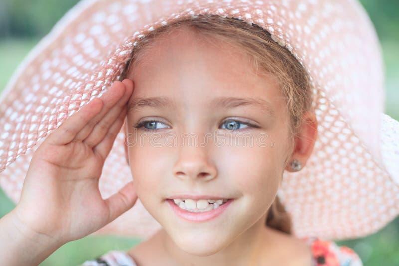 De zomerportret van een mooi meisje in een roze hoed stock fotografie