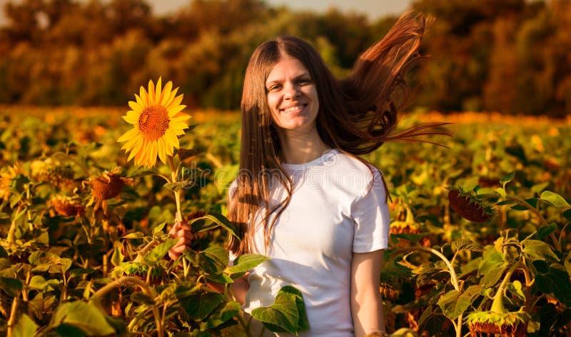 De zomerportret van gelukkige jonge vrouw in hoed met lang haar op zonnebloemgebied stock afbeeldingen