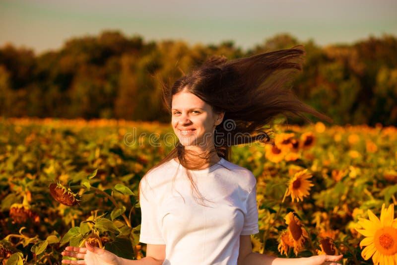 De zomerportret van gelukkige jonge vrouw in wit met vliegend haar op gebied royalty-vrije stock foto