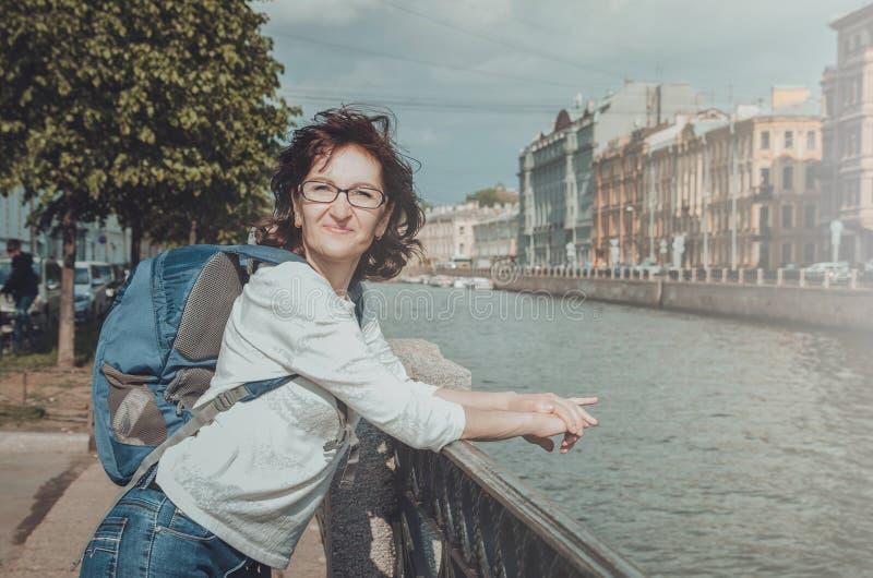 De zomerportret van gelukkige middenvrouwentoerist met glazen, gekleed in toevallige witte blouse, blauwe rugzak op haar stock fotografie