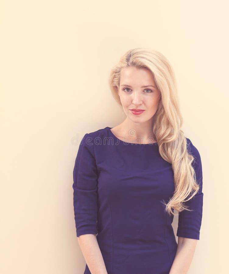De zomerportret van jonge mooie blonde vrouw in het blauwe kleding stellen dichtbij de muur Gestemd in warme kleuren royalty-vrije stock afbeelding