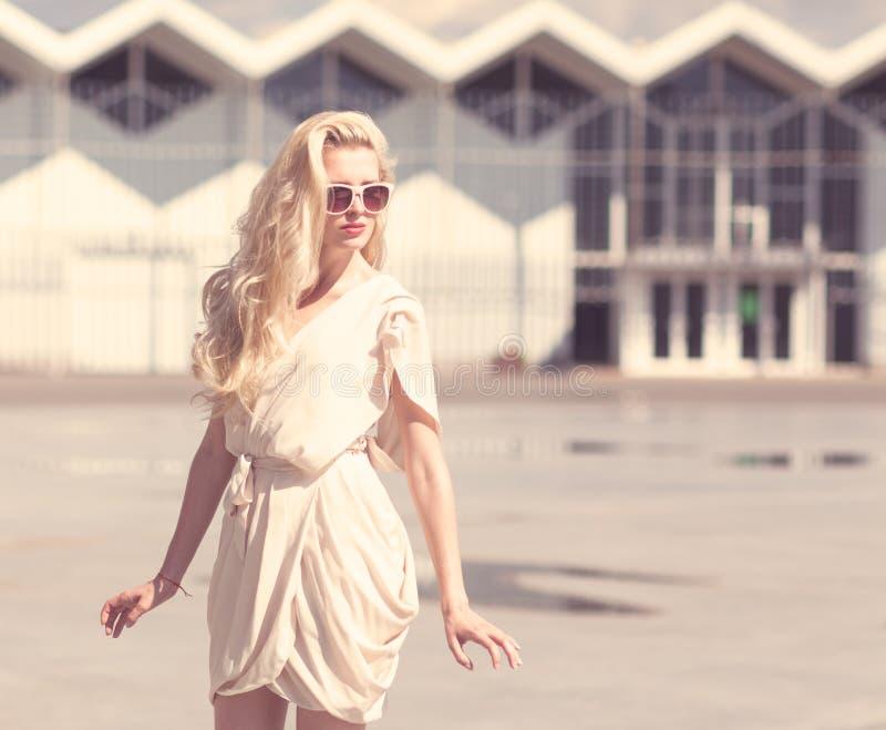 De zomerportret van jonge mooie blondevrouw in het witte de zomerkleding stellen Gestemd in warme kleuren stock foto