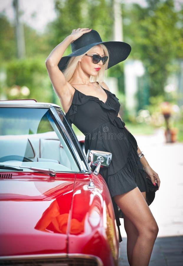 De zomerportret van modieus blonde uitstekende vrouw met lange benen die dichtbij rode retro auto stellen modieus aantrekkelijk e royalty-vrije stock foto's