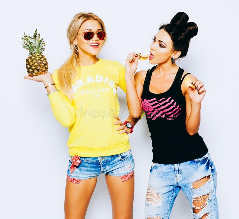 De zomerportret van twee vrij blonde en donkerbruine meisjesvrienden die pret met ananas, spaanders hebben Het zingen met zonnebr stock afbeelding