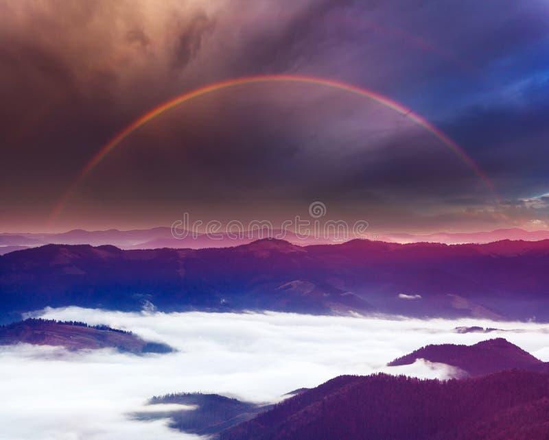 De zomerregenboog in bergen stock foto's