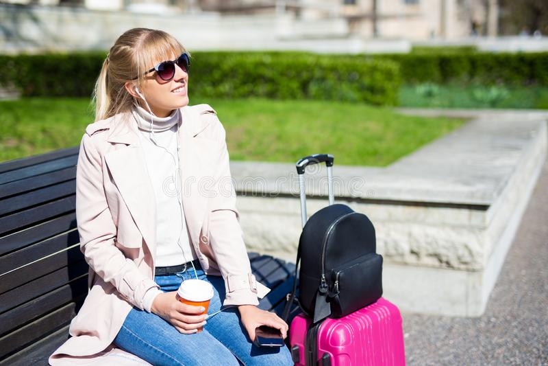 De zomerreis en vakantieconcept - jonge vrouwenzitting met koffer in park en het genieten van de van zomer royalty-vrije stock afbeeldingen