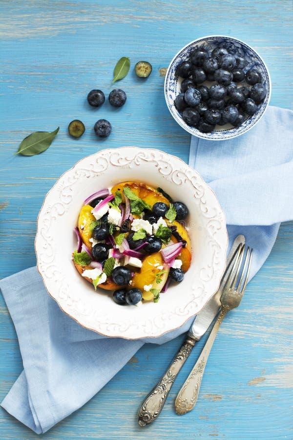 De zomersalade met geroosterde perziken, bosbes en feta-kaas royalty-vrije stock afbeelding