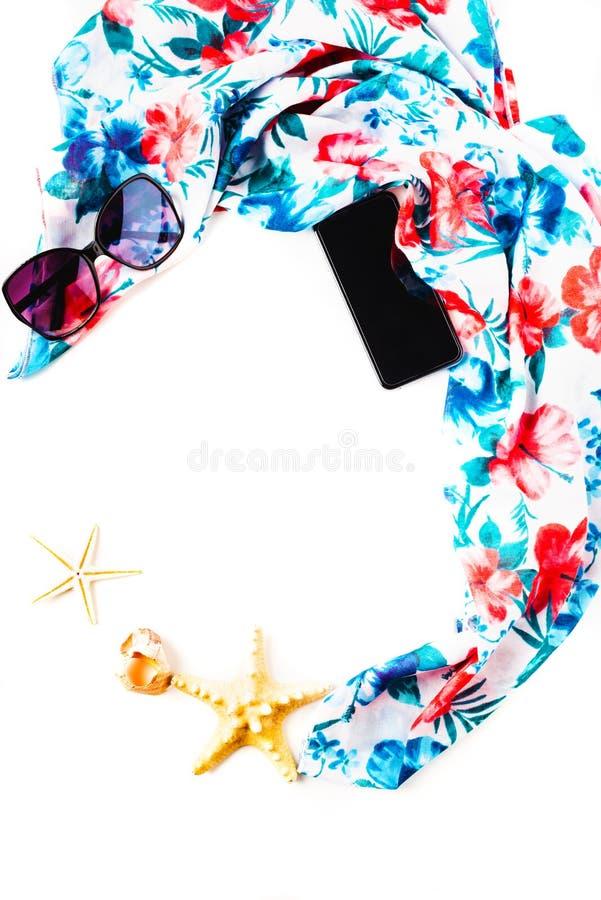 De zomersamenstelling - strandsjaal van bloemen, pareo, zonnebril, mobiele telefoon, shell, overzeese die sterren op een wit word stock foto's