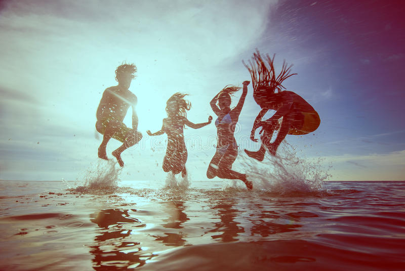 De zomersilhouetten van gelukkige jongeren die in overzees op B springen royalty-vrije stock afbeeldingen