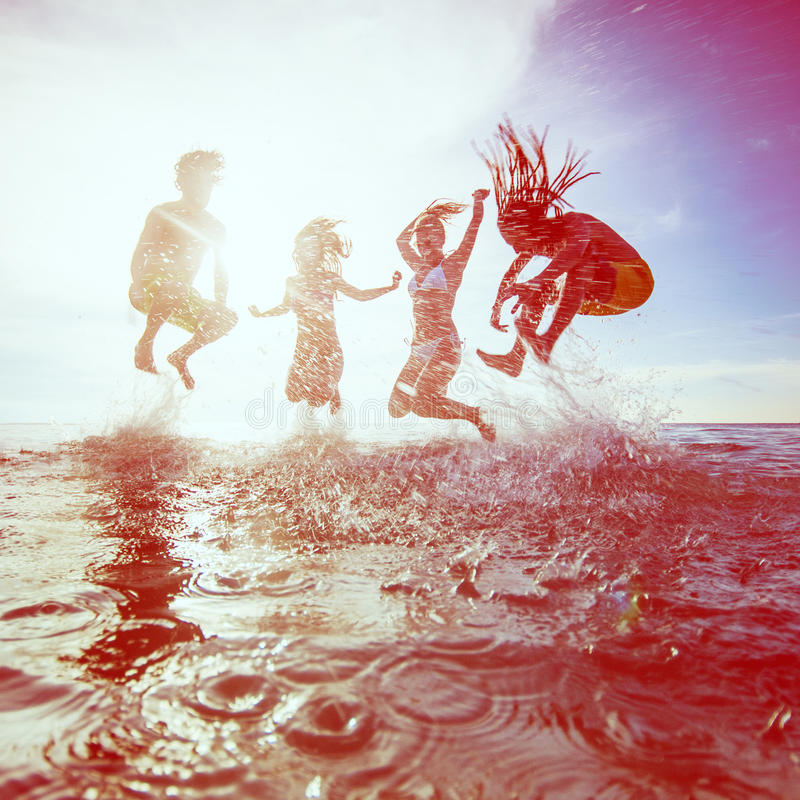 De zomersilhouetten van gelukkige jongeren die in overzees op B springen stock fotografie